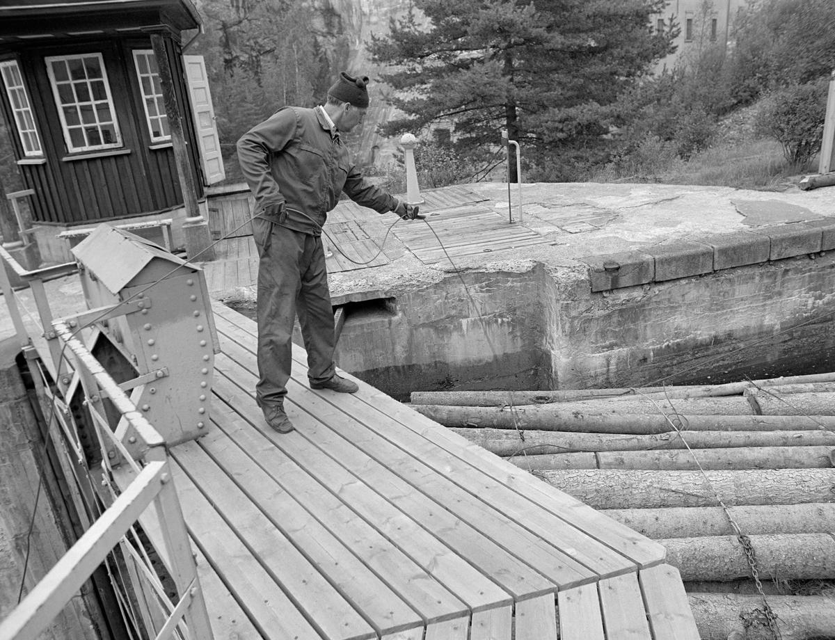 Fra Brekke sluser i Stenselva i tidligere Berg herred i Østfold. Fotografiet er tatt på en av sluseportene, der det sto en kar og hektet en krok i enden av en tynn vaier på det fremste vaierbindet på den fremste tømmerbunten i ovenforliggende slusekammer, som snart skulle tappes ned.  Brekke sluse har en løftehøyde på 27 meter fordelt på fire slusekammere.  Slusekamrene ble bygd i armert betong, og de høye, kraftige sluseportene var utført i stål.  Anlegget hadde hydraulisk styring av portene og vannstrømmen i omløpsrørene som førte vann fra ovenforliggende til nedenforliggende slusekammer.  Disse funksjonene ble styrt fra bryterpaneler i små «kiosker» ved sluseportene.  Her ser vi en slik kiosk til venstre, øverst på bildet.  Framfor kiosken ved den sluseporten var det en liten, framskutt plattform (ikke synlig på dette fotografiet, men blant annet på SJF-F.009355 og SJF-F.009358) der det sto et nokkespill med en vaierforbindelse ned på slusevendinga.  Denne innretningen ble brukt til å holde slusevendingene i riktig posisjon i slusekamrene, slik at de ikke lå i vegen når portene skulle åpnes. Det er vaieren fra dette nokkespillet mannen på dette fotografiet forsøkte å feste før kammeret ble nedtappet og portene ble åpnet.  En liten historikk om tømmerfløting og kanaliseringsarbeid i Haldenvassdraget finnes under fanen «Opplysninger».
