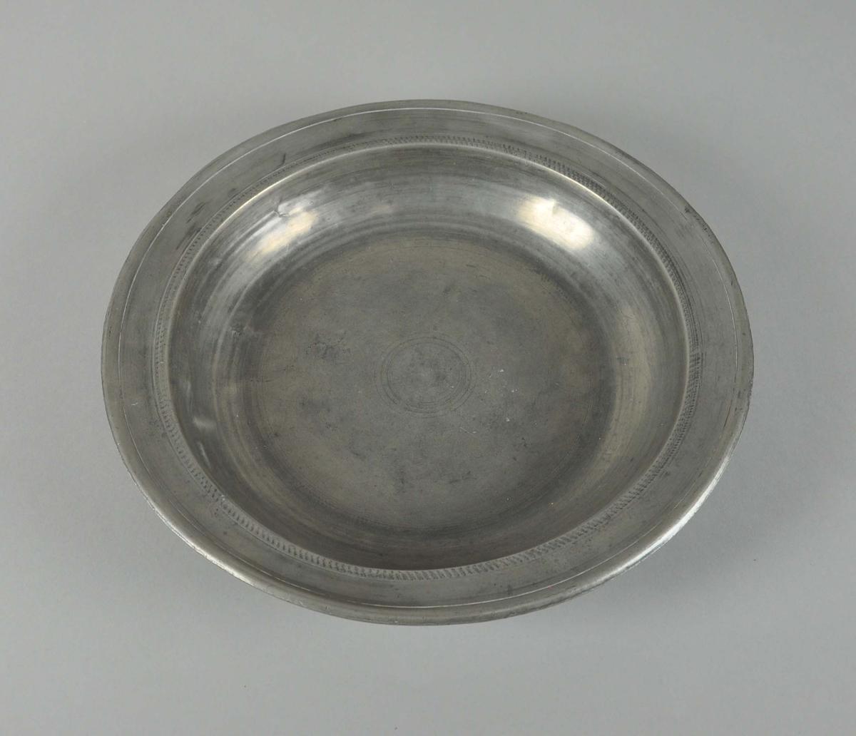 Rundt fat av tinn. Fatet har opphøyd og utstående kant, konsentriske sirkler er dekorativt risset inn i fatet. Metallet er noe bulket.