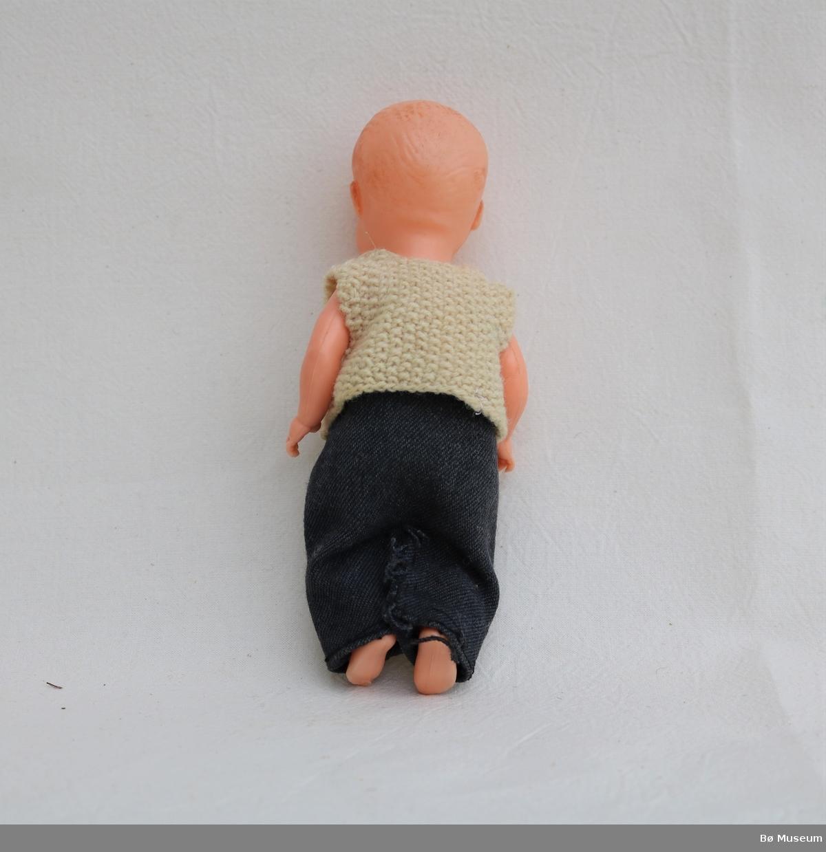 Babydokke med strikka vest og bukse. Buksa er heimelaga og grovt tråkla med trykknapp i livet. Vesten har eit hol. Dokka har måla ansikt og hår der fargen er nesten heilt slitt vekk. Innfelte auge. Armar og bein er bevegelege.