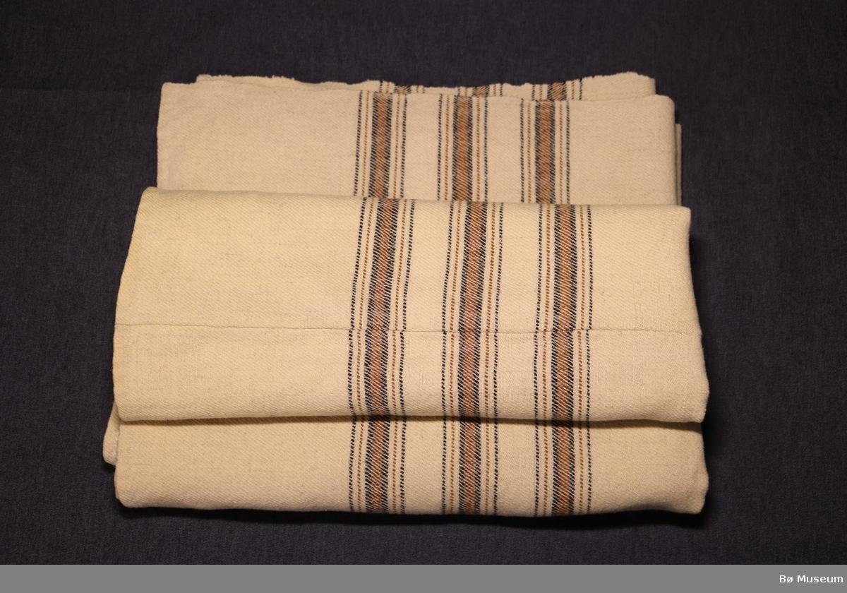 Stripete, heimevevd ullteppe. Sydd saman av to like store stykke. Fall oppe og nede.