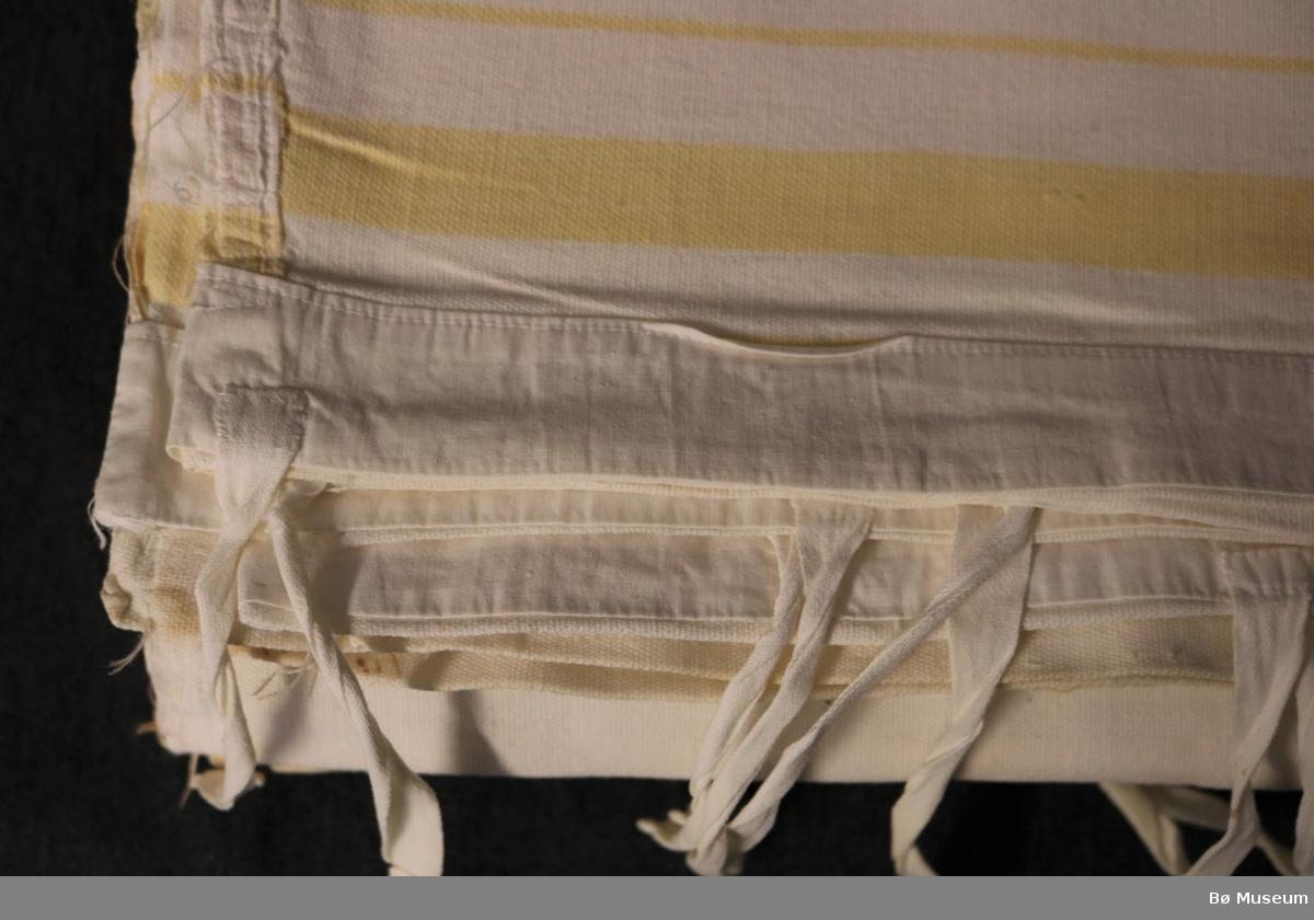 Stripete dynetrekk med opning og bendelband til knyting i eine enden. Omsydd, har knappehol (ute av bruk, sydd igjen). Samansydd på midten i lengderetningen. Begge kortsidene har skonering. Litt sliteskadar og nokre brune flekkar.