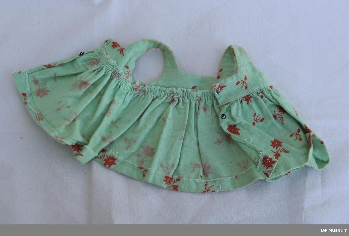Dokkekjole med babydollsnitt og skulderstroppar. To trykknappar i ryggen. Skjørtet er sydd fast i overdelen med rynker. Det er trykt mønster av blomar og blad på stoffet. Litt slitt og nuppete.