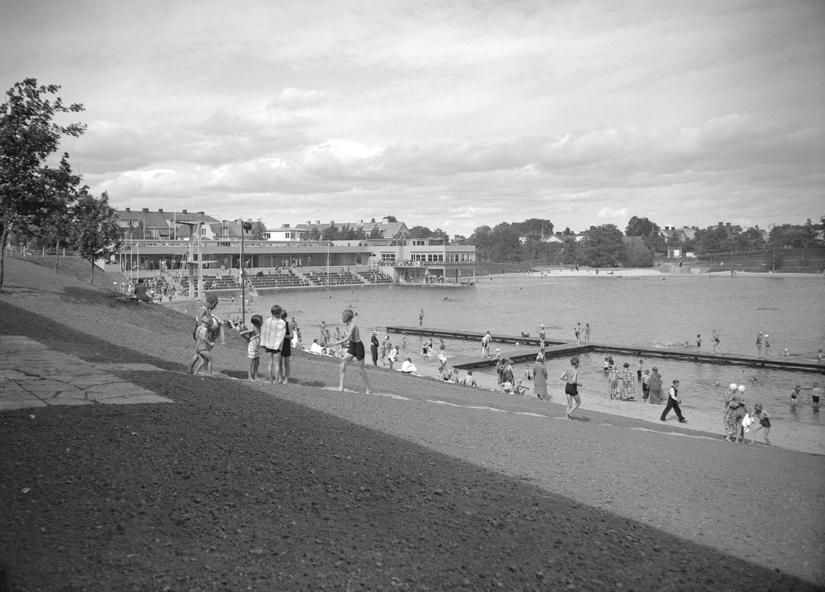 Vy över Tinnerbäcksbadet i Linköping 1938. Det är badets första sommar, tillkommet efter lång diskussion med starka inslag av kritik kring de uttjänta och ohygieniska kallbadhusen i Stångån. Anläggningens slutliga utformning skapades av stadsarkitekten Sten Westholm. Den tidstypiska entré-, omklädnads- och restaurangbyggnaden är i stort ännu orörd sedan den uppfördes. Den drivande politiska kraften bakom badet var köpmannen Axel Brunsjö. I vissa kretsar kallades badet för Brunsjön, efter köpmannens stora engagemang för badet. Badet fick sitt namn efter Tinnerbäcken som före anläggningens tillkomst runnit genom området.