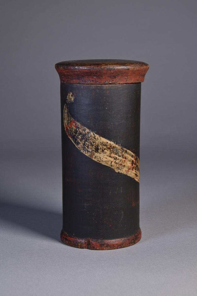 Ståndkärl, cylindriskt, av trä målat i svart med plant lock. Målad sköldformad etikett i gult med text i svart och rött. Texten i dag oläslig. På baksidan målat böljande band i gulvitt.