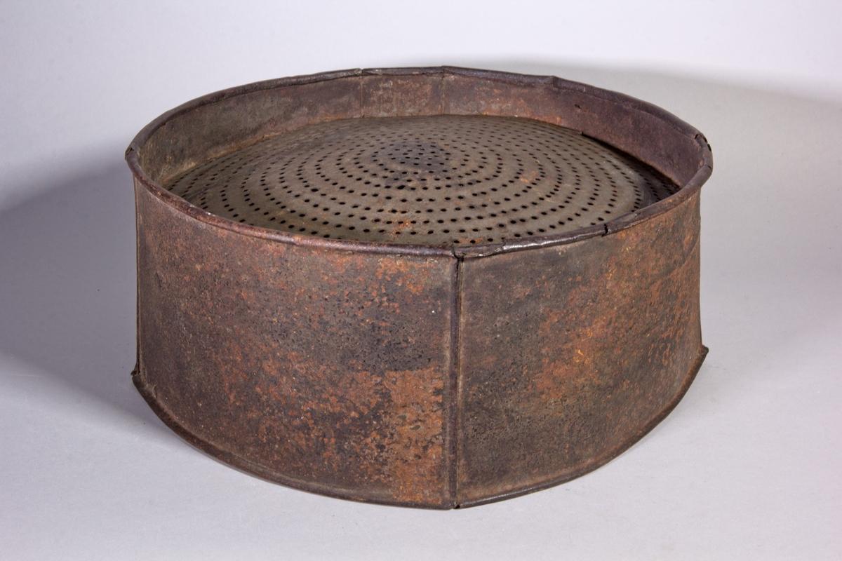 Perforat, cylindriskt av järnbleck med perforerad botten.