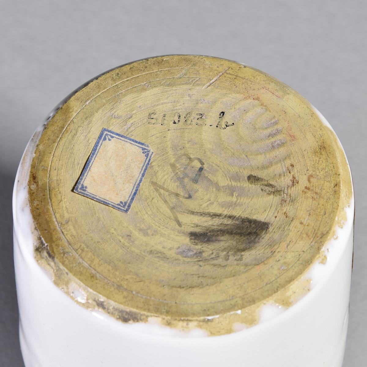 Apoteksburk av vitglaserad fajans, cylindrisk med rundad skuldra, indragen hals. Välvt lock med fals och rund lockknopp. Rester av sekundär etikett.