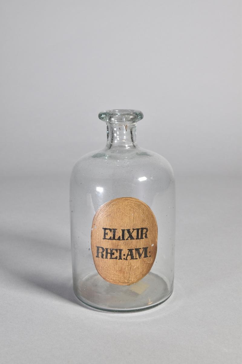 Flaska av klart glas, cylindrisk, kort hals med utsvängd mynning. Påmålad etikett med svart text.
