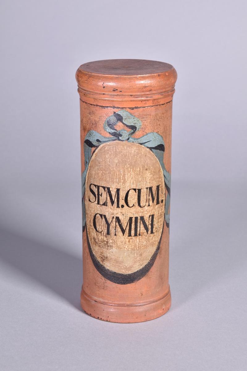 Ståndkärl av rödmålat trä, cylindriskt med plant lock. Svart text inom oval med bandrosett.