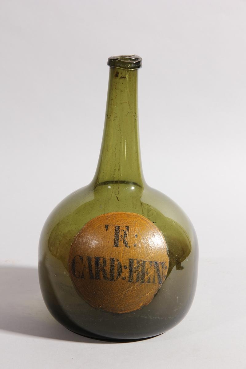 Flaska av grönt glas, rund med flat botten och hög hals.