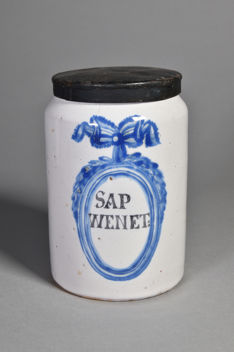 Apoteksburk, ståndkärl, av vitglaserad fajans, cylindrisk. Text inom blåmålad medaljong med rosett. Lock av bleckplåt, målat, med rester av foliering.