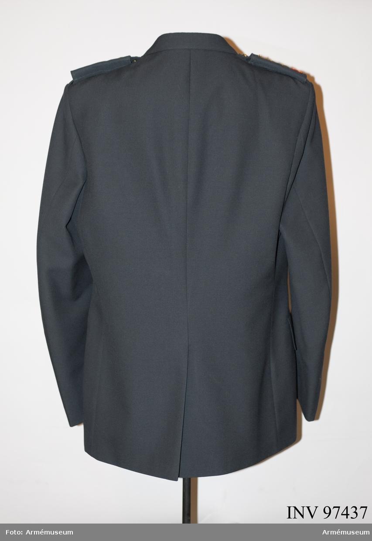 Vapenrock i ull och polyester, tillverkad i Jugoslavien 1987. Med axelhylsor för apotekare med kaptens gradbeteckning och fältläkarkårens knappar.