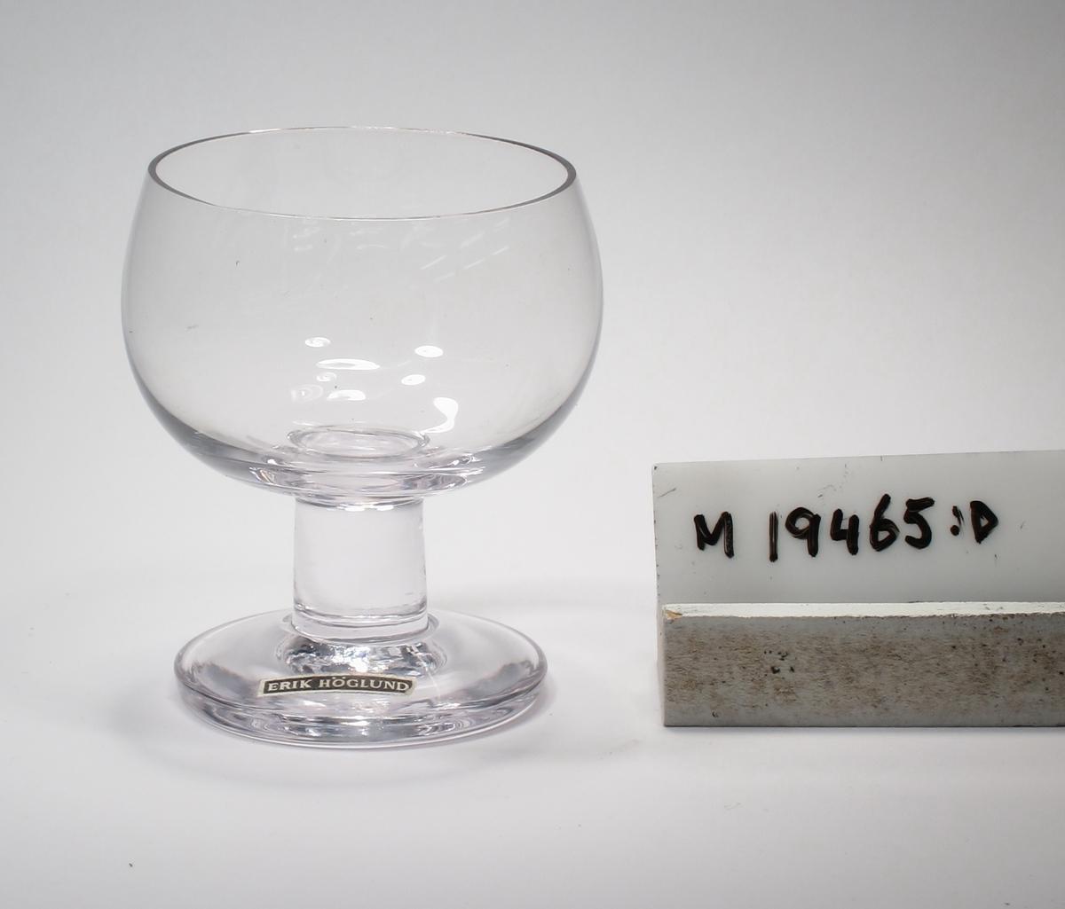 """Glas på ben och fot, tillhörande servis """"H 6"""". Formgivet av Erik Höglund. Skål något rundad nedtill och något avsmalnande upptill.  Benet cylindriskt. Ofärgat klarglas. Ovan angivna mått avser övre diameter. Inskrivet i huvudkatalogen 1968. Funktion: Glas"""