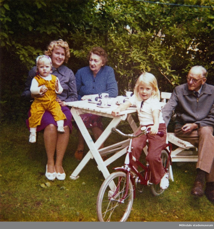 """En grupp människor sitter och dricker kaffe i bersån, Kryssgatan 18 (""""Stusshålan"""") i Mölndal. Från vänster Berit Gustafsson med dottern Christine i knäet, därefter Berits mor Anna Larsson (född Hasselberg), storasyster Ingela på cykel och morfar Ernst Larsson."""