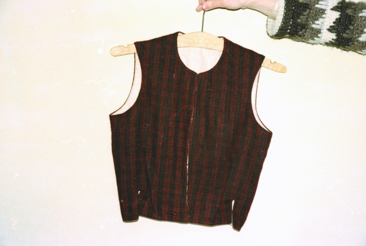 Et koneliv i rutet rødt fra Massgarden, Linge. Brukt mest om sommeren, uten bluse under. Motiv tatt ved ei tekstilutstilling i Valldal.