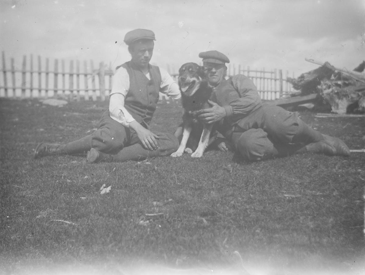 To menn sitter på grassbakken med hund