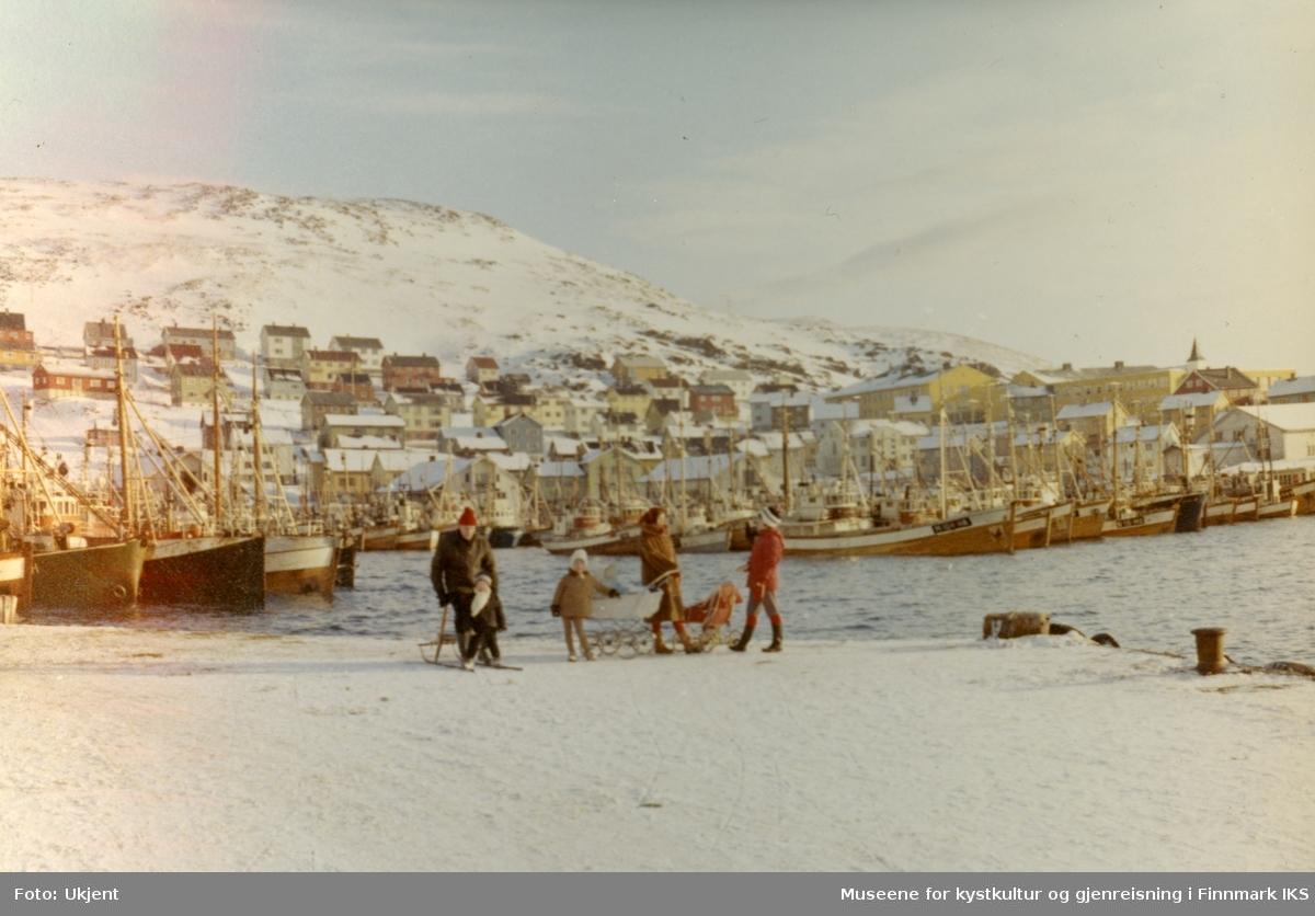 Honningsvåg. Deler av bebyggelsen. Mange fiskebåter i Indre havn. Flere personer på kaia. Mars/april 1966.