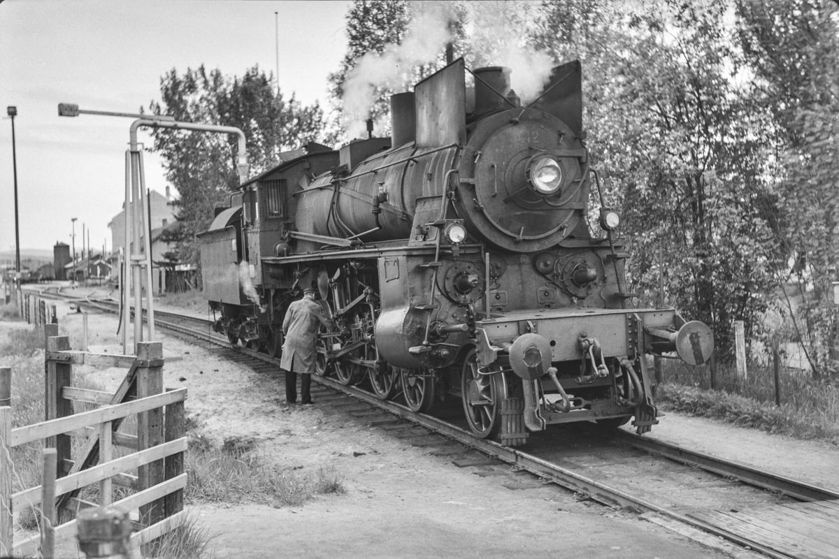 Vannfylling fra vannstender på damplokomotiv type 26c nr. 412 på Tynset stasjon. Lokomotivet benyttes på strekningen Tynset-Hamar i underveisgodstoget fra Trondheim til Hamar over Røros, tog 5712.