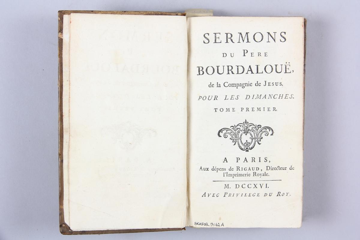 """Bok, helfranskt band, """"Sermons du Pere Bourdalouë"""" del 1, tryckt i Paris 1716. Skinnband med guldpräglad rygg med fem upphöjda bind. Titelfält med blindpressad titel, rödstänkt snitt. Etikett med samlingsnumret."""