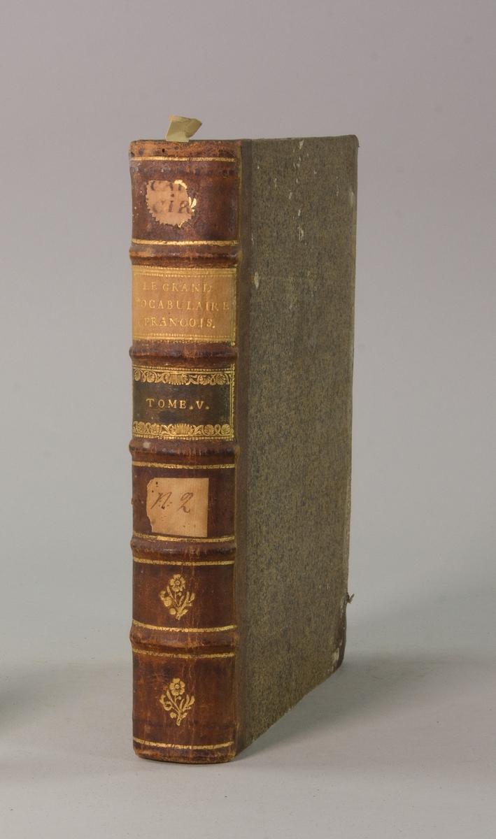 """Bok, halvfranskt band """"Le grand vocabulaire francois"""", del V, utgiven i Paris 1768. Band med pärmar av papp med påklistrat stänkt papper, hörn och rygg av skinn med fem upphöjda bind med guldpräglad dekor, titelfält med blindpressad titel och ett mörkare fält med volymens nummer. Med stänkt snitt. Påklistrade etiketter märkta med bläck """"No 2"""" och """"CAP CIRI""""."""