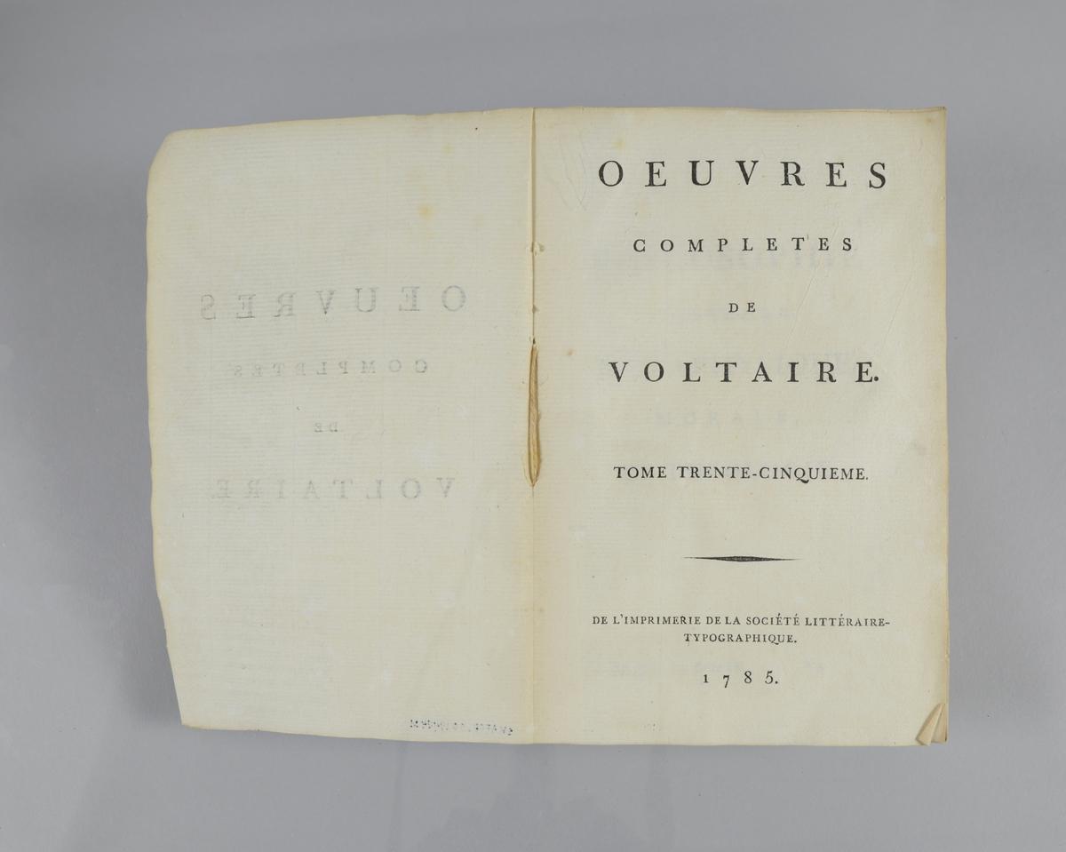 """Bok, pappband,""""Oeuvres completes de Voltaire"""", del 35, tryckt1785. Pärmen klädd med gråblått papper, på pärmarnas insidor klistrade sidor ur annan bok. Med skurna snitt. På ryggen klistrad pappersetikett med tryckt text samt volymens nummer. Ryggen blekt."""