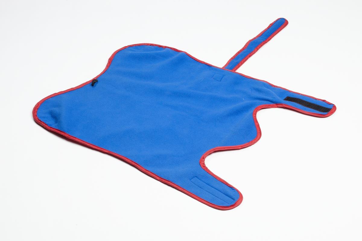 Hundedekkenets overside er rødt og undersiden er blå. Oversiden er i et blankt kunnstoff og undersiden er myk flece. Hundedekkenet har to flapper i den ene enden som festes rundt benene til hunden med velcro lukning. I den andre enden finnes en liten sort stropp. Hundedekkenet har to stropper i den ene siden som festes rundt magen til hunden med velcro lukning.  Hundeposene er gitt av en av museets medarbeider til museet i forbindelse med Hundeprosjektet 2007 til utstillingen Hunden - Menneskets beste venn. Hunden Lille My har brukt hundedekkenet.  Gjenstanden er samlet inn i forbindelse med Hundeprosjektet 2006-2007 Husdyr på museum - Et fellesprosjekt i Akershusmuseet 2007