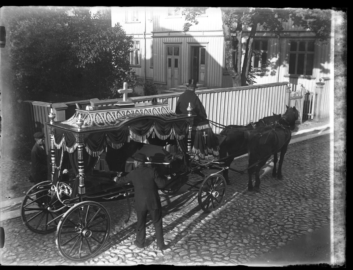 """Två svarta hästar drar en begravningsvagn som körs av en kusk i svart stormhatt och svart mantel. Två män står på varsin sida om vagnen. I fotografens inventering står: """"Fru Nilssons begrafning""""."""