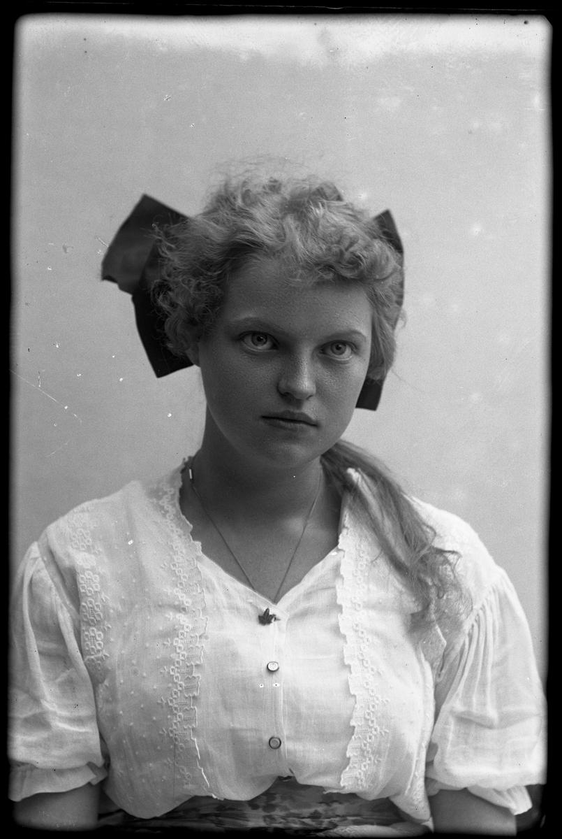 Porträtt av Greta Bengtsson i vit klänning och med mörk rosett i håret.
