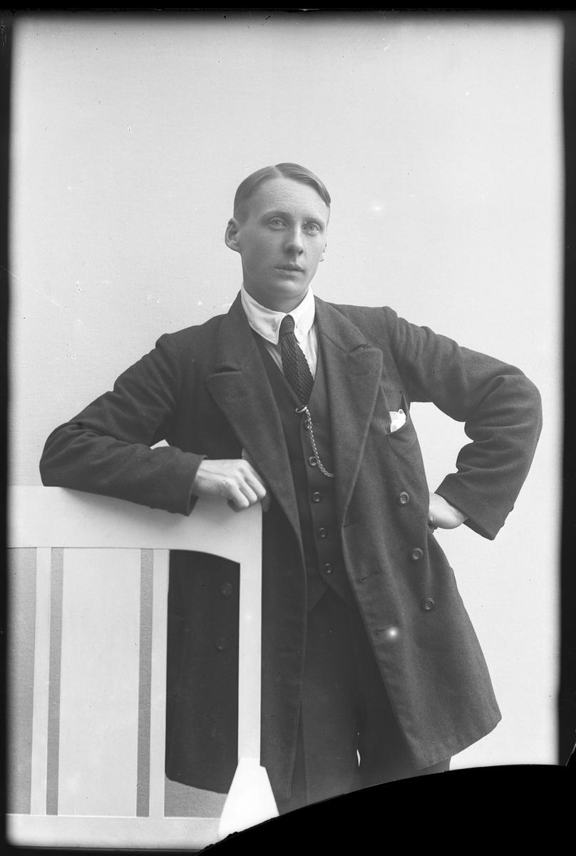 Porträtt av Karlström, iklädd tredelad kostym, vit skjorta och slips, lutad mot en stol.
