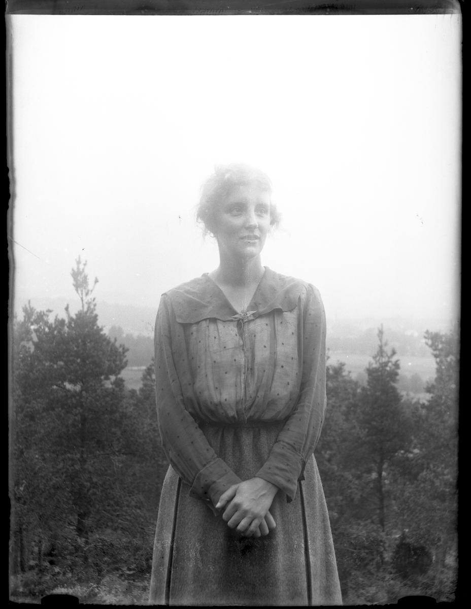 Porträtt av Ellen Andersson med händerna knäppta framför sig.
