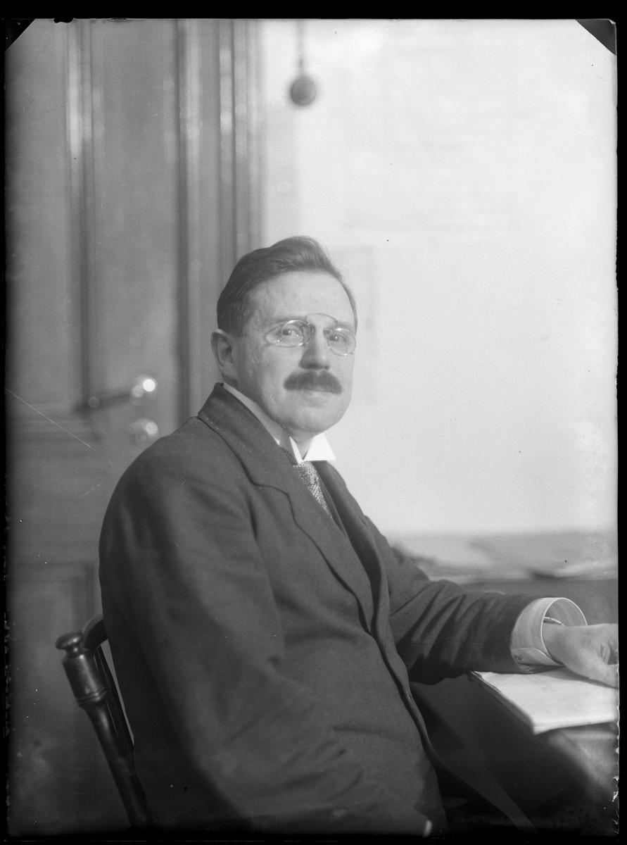 Herr Petersén (eller Petterssén) fotograferad sittandes vid ett skrivbord.