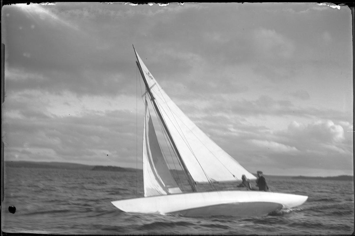 """Segelbåten """"Yssa"""" fotograferad i samband med kappsegling. Ombord syns två personer."""