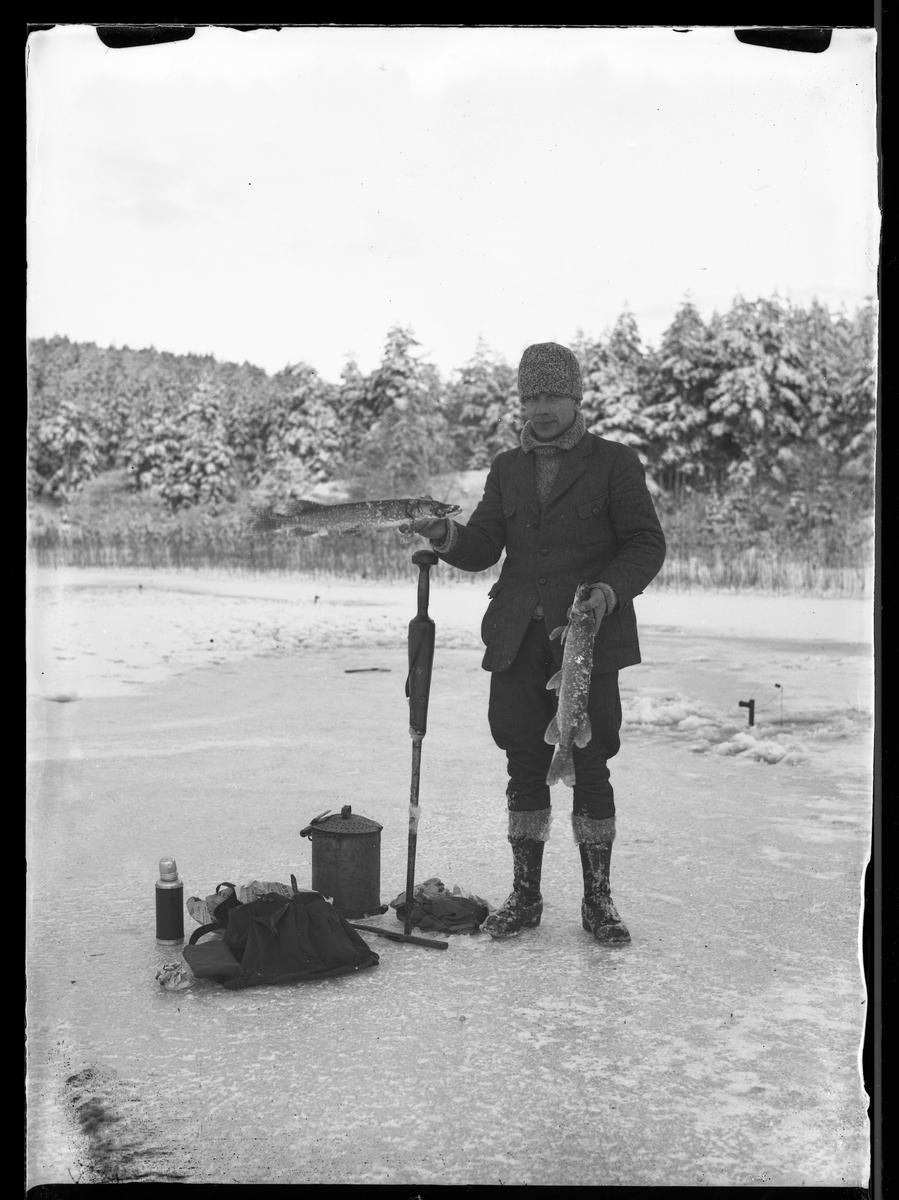 """En man står på isen med två fiskar i handen, bredvid honom ligger redskap och fika. I fotografens egna anteckningar står det """"Angelfiske på Kvarnsjön"""""""
