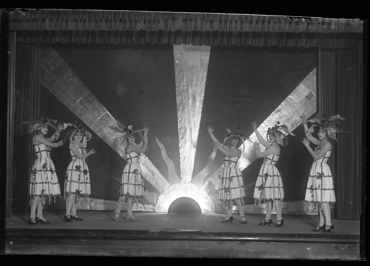 Sex kvinnor står på en scen och spelar nyårsrevy.