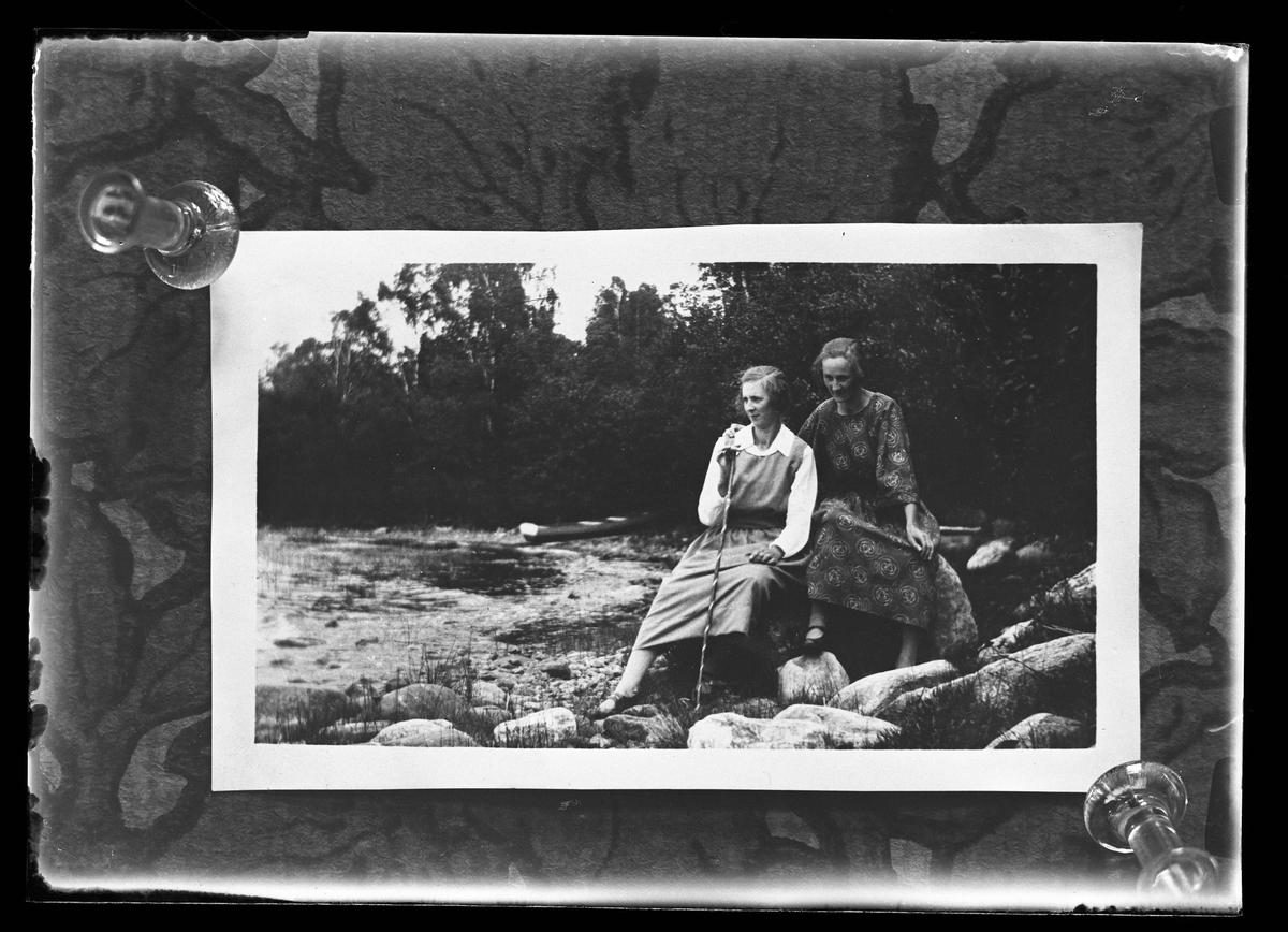 """Reprofotografi av en bild på två kvinnor som sitter på några stenar vid en strand. Den ena kvinnan håller i den andra som har en käpp i handen. I bakgrunden syns en båt. I fotografens egna anteckningar står det """"Rep. för Eliasson""""."""