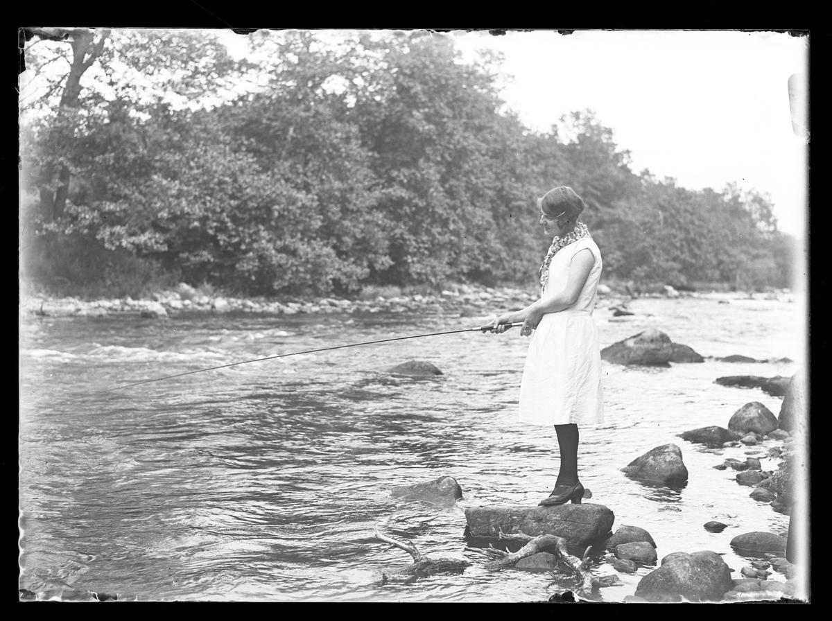 Lizzie Skoglund står på en sten i vattnet och metar.