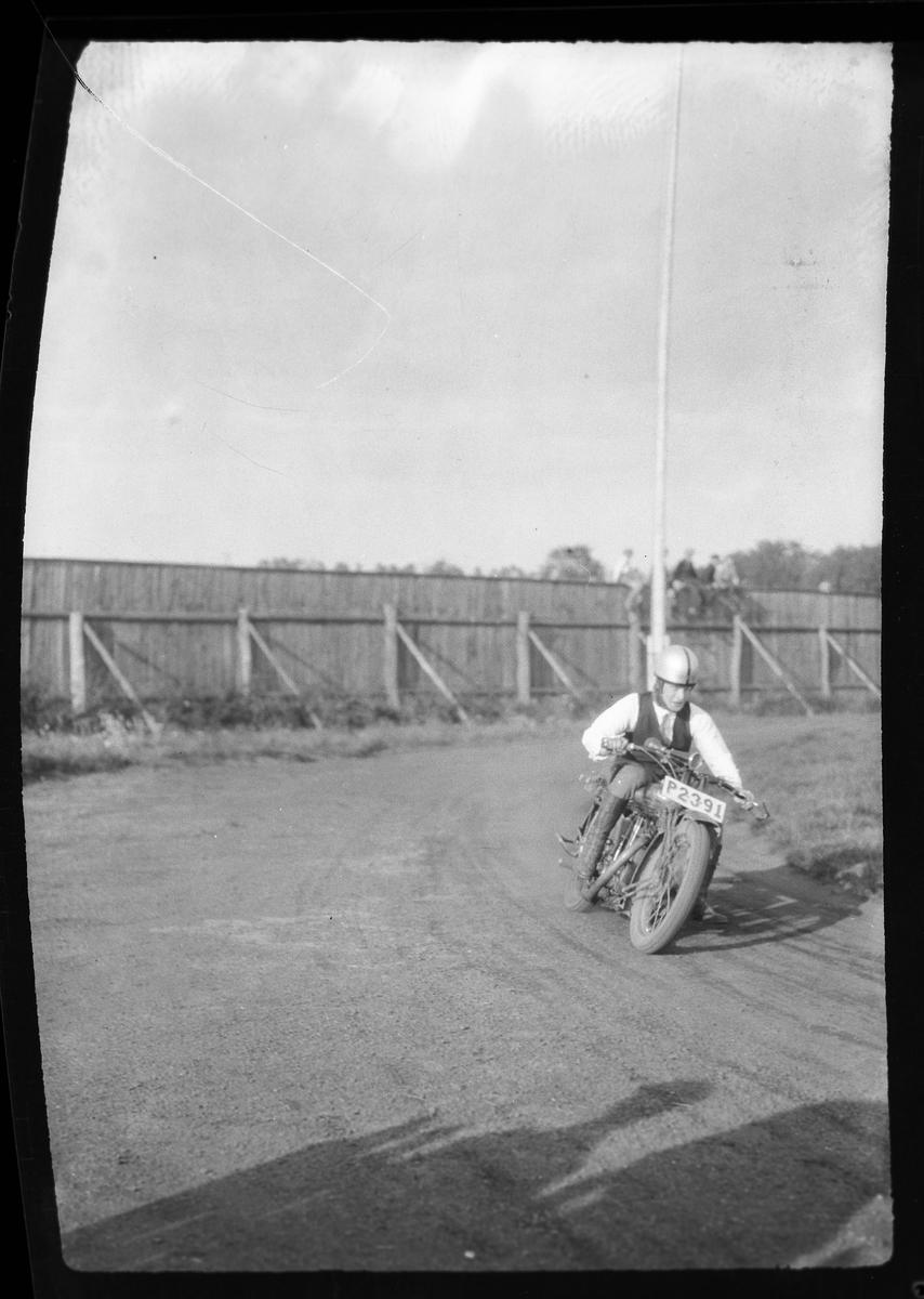"""En man kör motorcykel på en grusad bana. I fotografens anteckningar står det: """"2 film från Motorcykellopp (Idrottsp.)""""."""