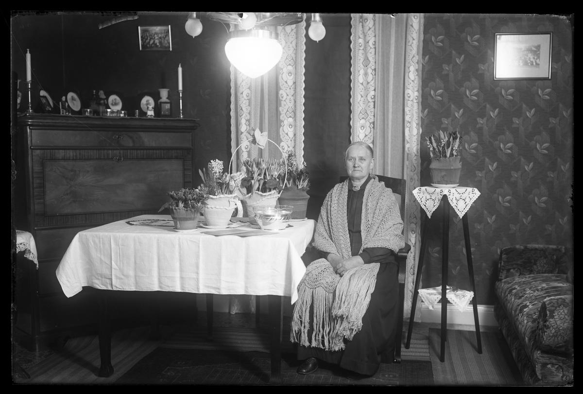 Fru Andersson fotograferad i ett finrum tillsammans med blommor och presenter i samband med sin 70årsdag.