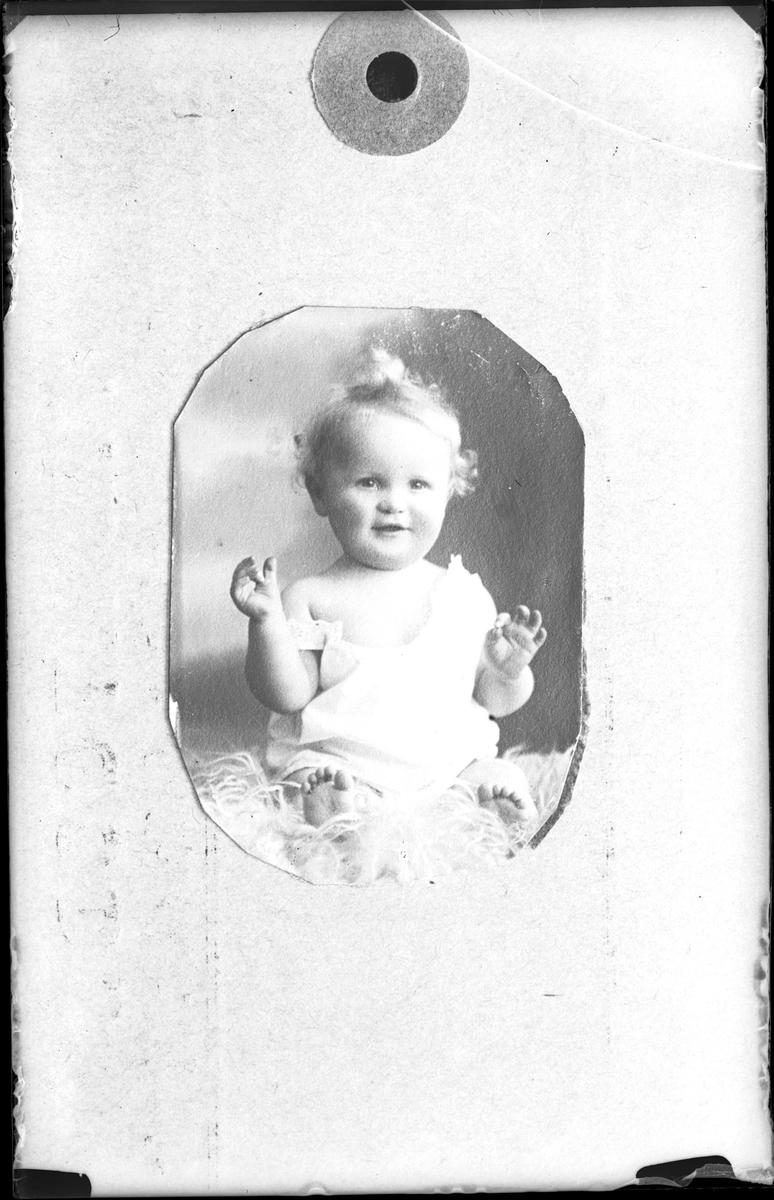 Reprofotografi på ett porträtt av ett barn i vita kläder.
