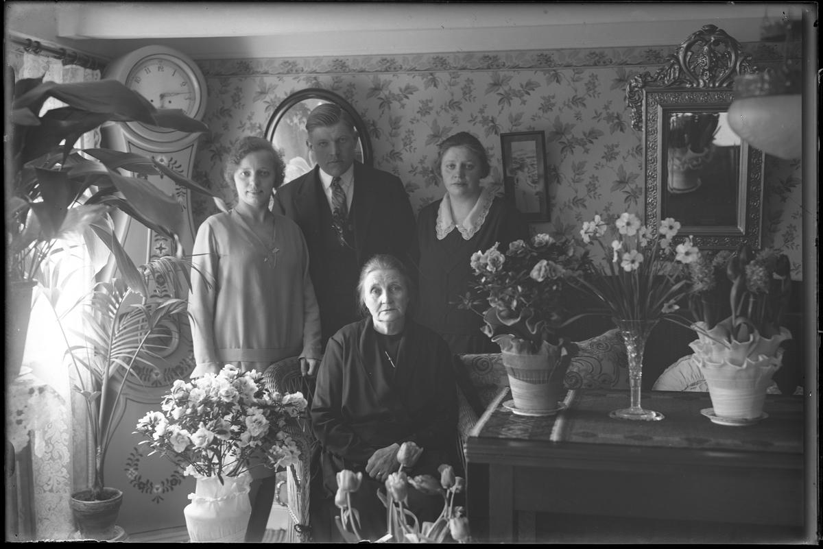Fru Pettersson fotograferad i ett finrum tillsammans med blommor i samband med sin 65årsdag. Bakom henne står hennes familj.