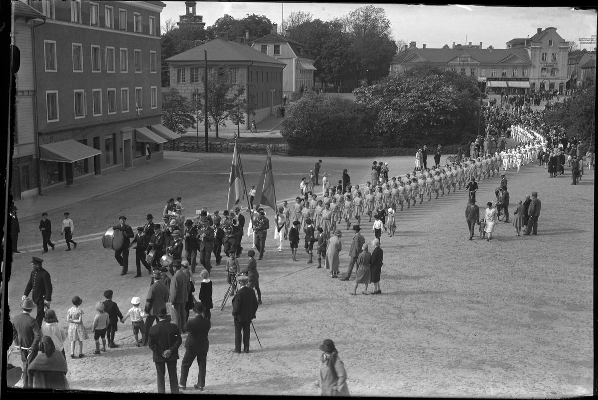 Musikanter och gymnaster går i en parad över Stora och Lilla torget. Runt om står människor och tittar på. Paraden hölls i samband med Gymnastikfesten på Idrottsplattsen.