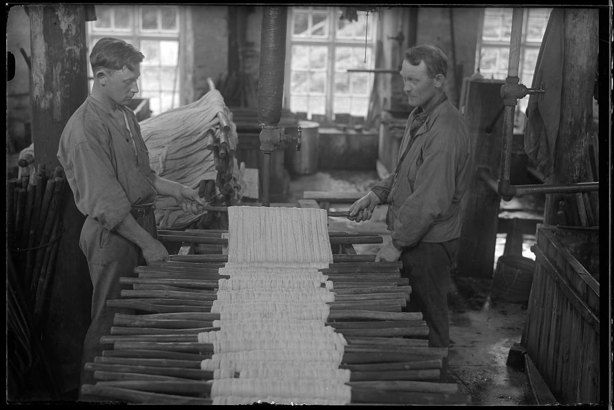 Verksamhetsbild från Nääs Fabriker där två personer arbetar med garnhärvor vid ett bord.