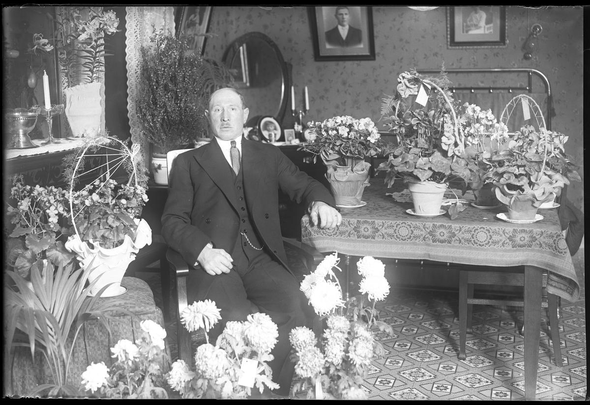 """En man sitter vid ett bord i ett finrum, omgiven av blommor i samband med sin 50årsdag. I fotografens egna anteckningar står det """"Gustaf Johanssons 50 år"""", tolkat som Anders Gustaf Johansson."""