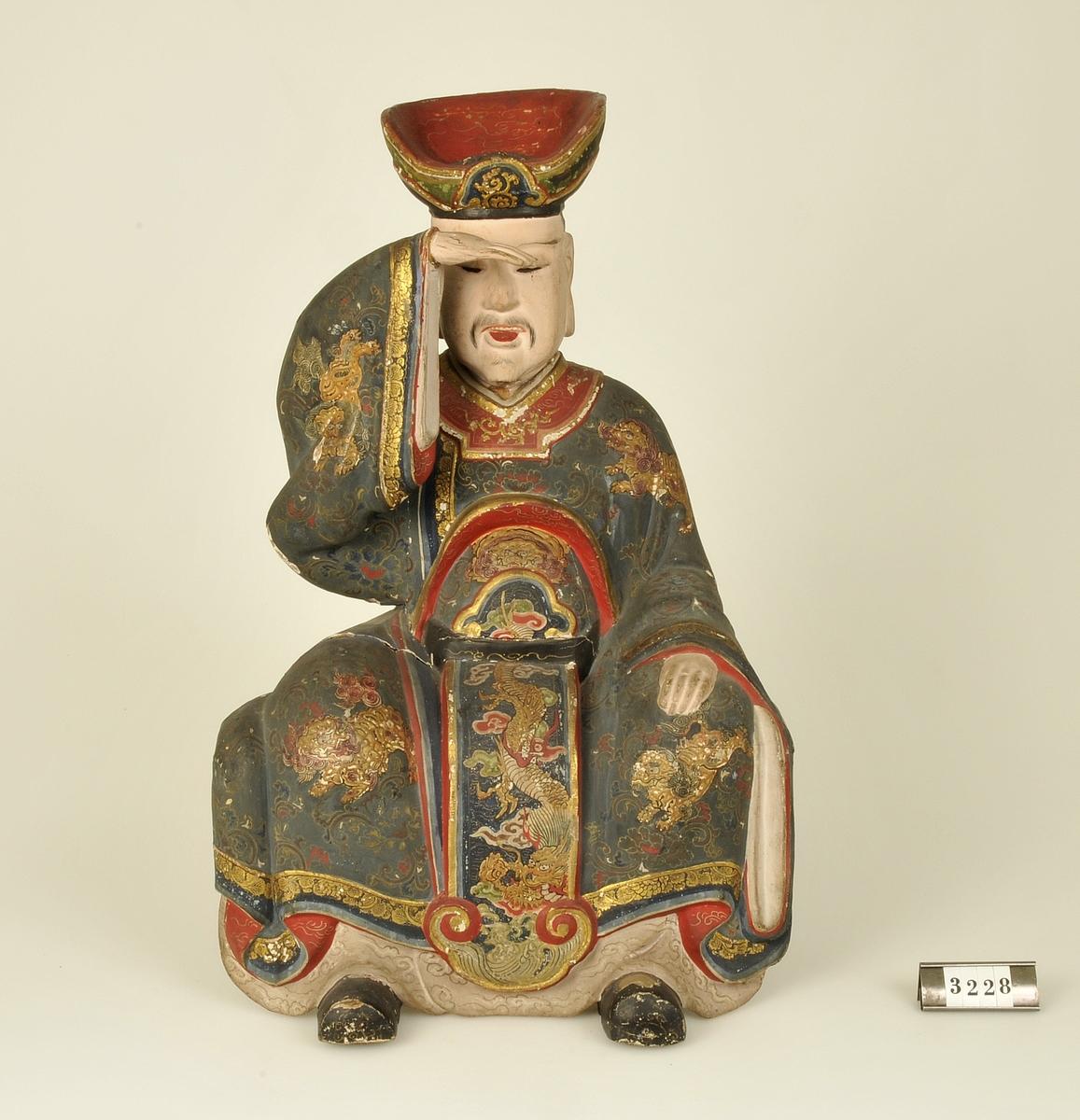 Skuren i trä. Man i sittande ställning målad i svart, guld och rött. Håller handen för ögonen.  Har tillhört de Adelsköldska samlingarna.