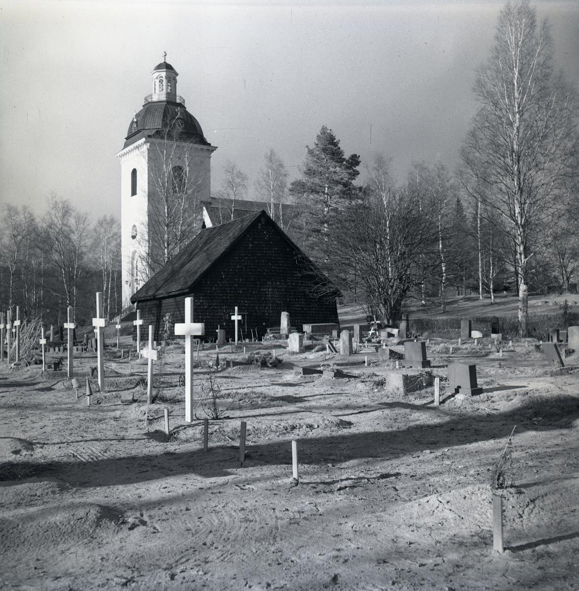 Färila kyrka delvis dold bakom en byggnad.
