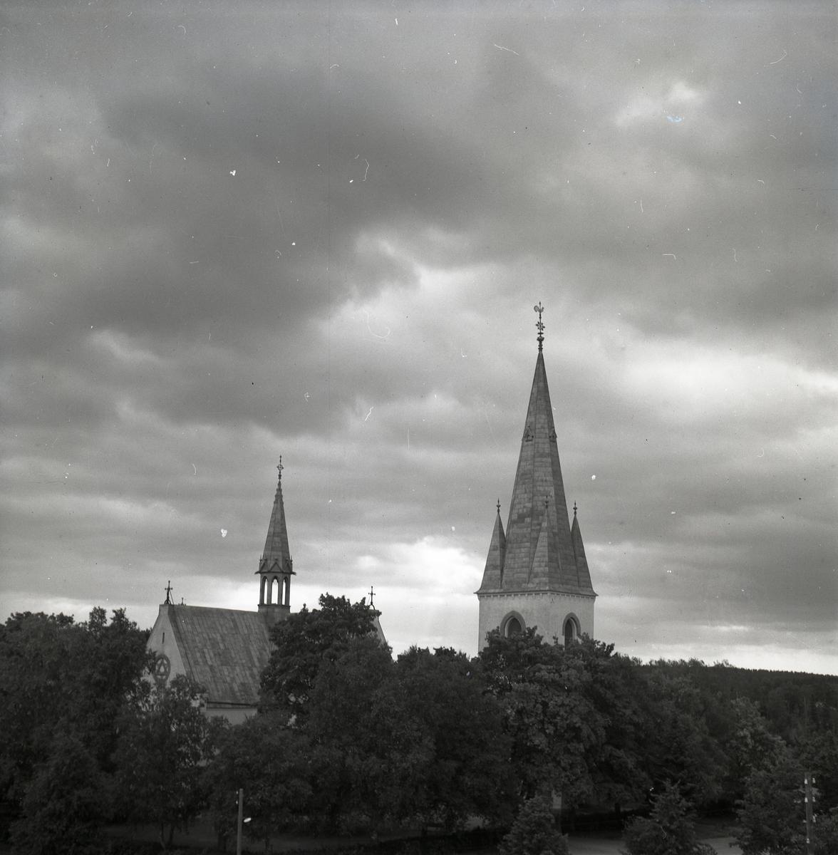 Bland trädtopparna sticker kyrktornet och takryttaren från Harmångers kyrka upp.