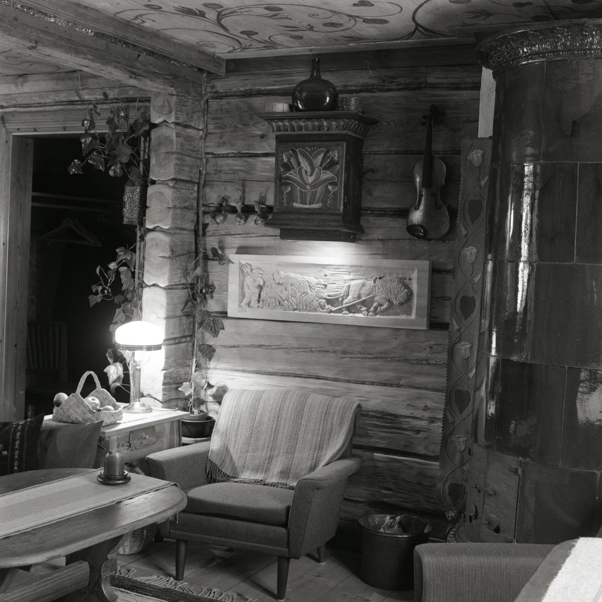 Ett rum på gården Sunnanåker med en snidad reliefbild, väggskåp, fåtölj, fiol och kakelugn, 1972.