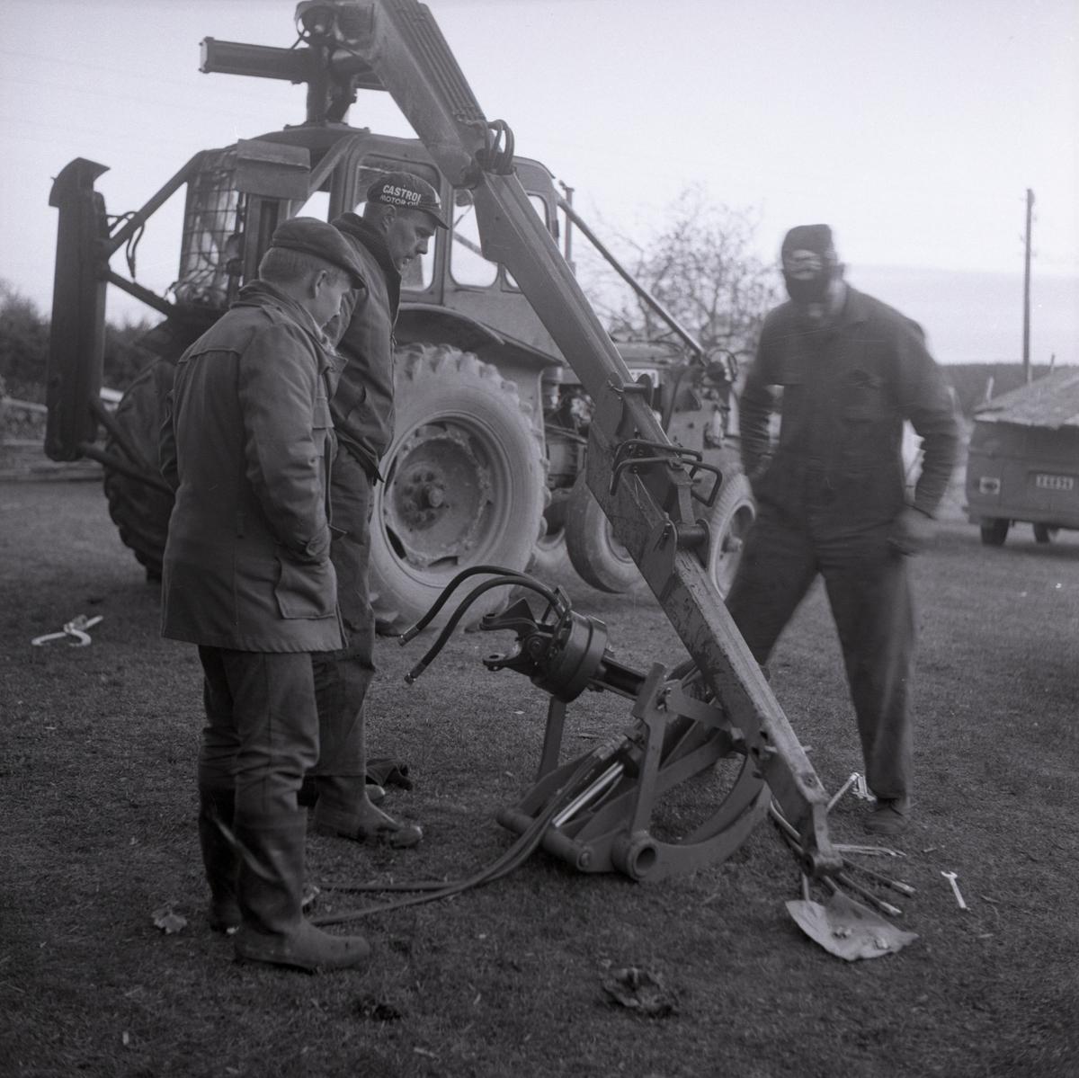 Tre män inspekterar en gripklo till en traktorn i Rengsjö, 1967.