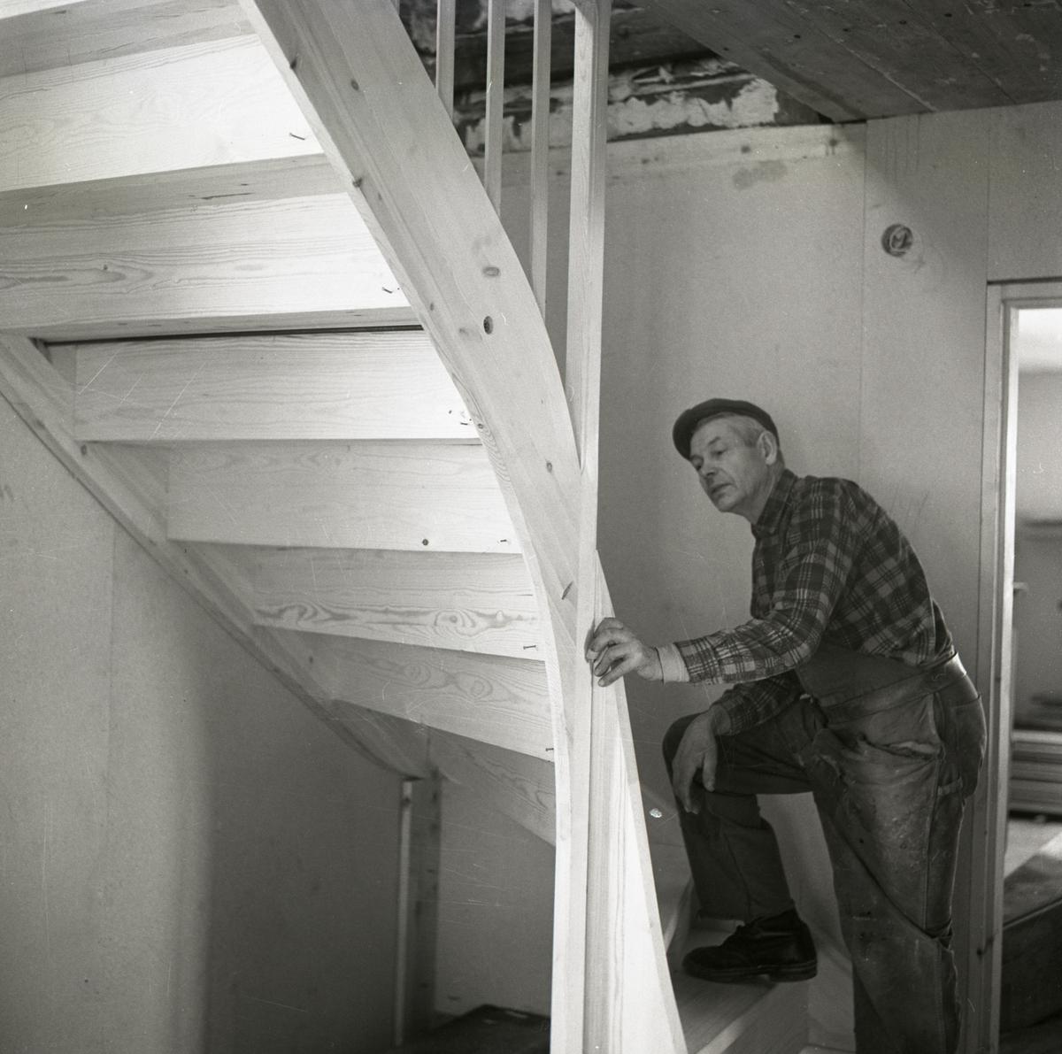 En man inspekterar en trappa i ett hus på gården Sunnanåker, 1967.