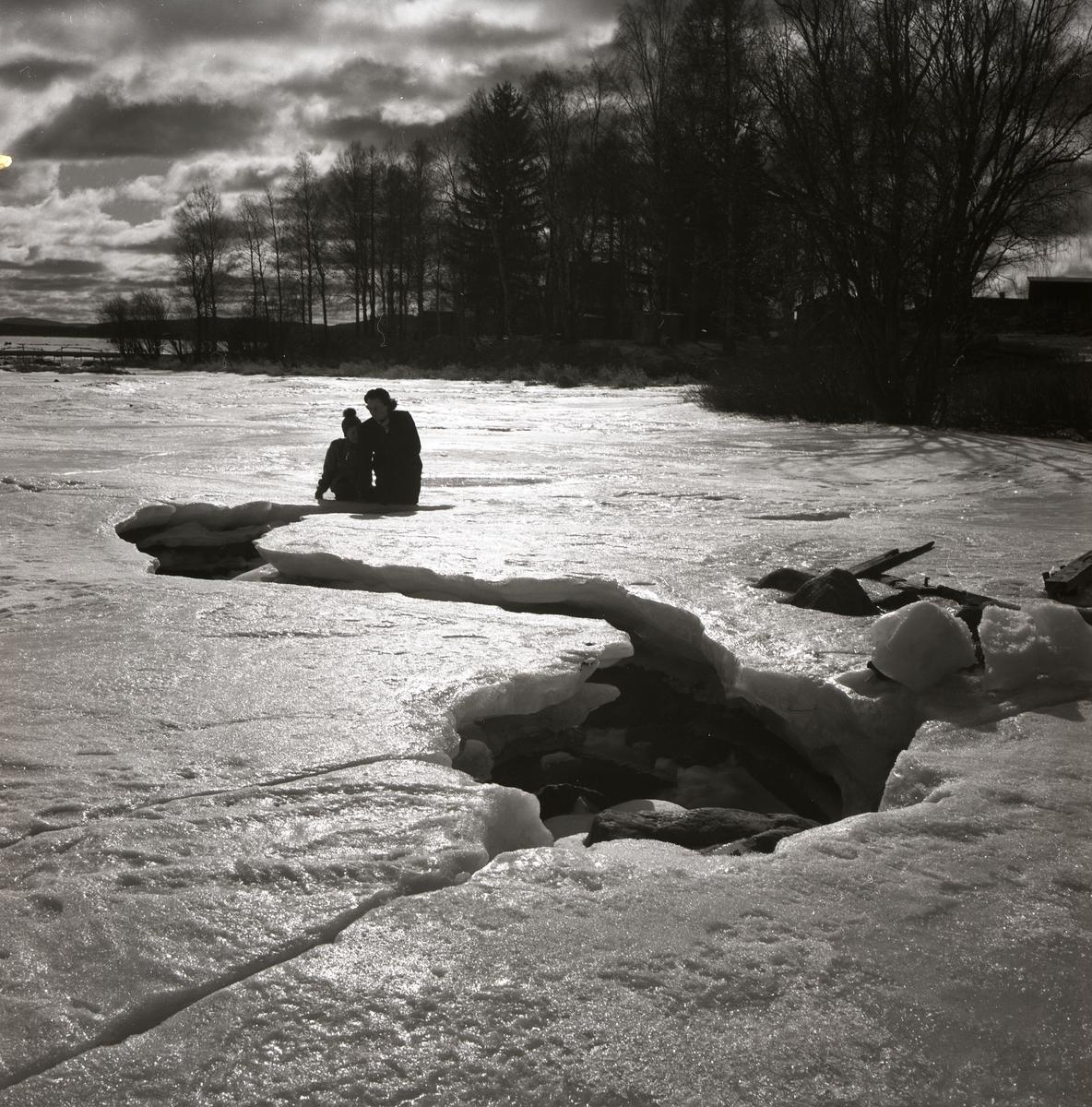 Intill en stor isspricka, någonstans i Bollnäs, sitter Hildings fru och son den 16 mars 1952.