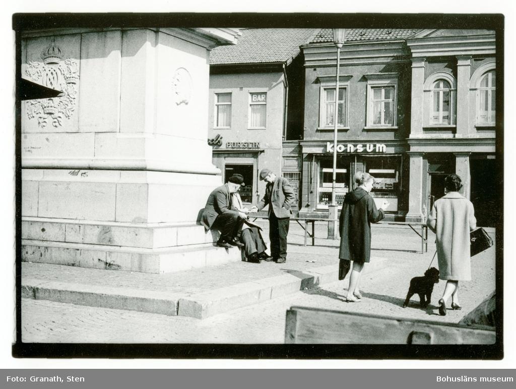 """Kungstorget i Uddevalla. Den vänsta halvan av bilden domineras av fundamentet till Dubbelstatyn vid vilken tre män samlats och samtalar. En stående man ger eller får något av en av de två män som sitter ner. Till höger i bild går två kvinnor från betraktaren. Den ena håller i en frukt(troligen ett äpple) och den andra håller en hund(troligen pudel) i koppel. I bakgrunden syns fasaderna till Konsum och en porslinsaffär. I ett av fönstren ovanför porslinsaffären finns en skylt """"BAR""""."""